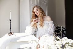 Girl writes a letter to her beloved man, sitting at home at table in a white light dress, purity and innocence. Curly blonde. Romantic look, beautiful eyes Royalty Free Stock Photography