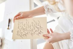Girl writes a letter to her beloved man, sitting at home at table in a white light dress, purity and innocence. Curly blonde. Romantic look, beautiful eyes Stock Photos