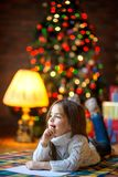 Girl writes a letter to santa claus. Beautiful girl writes a letter to santa claus lying on the floor, in the background festive lights on the Christmas tree Royalty Free Stock Photo