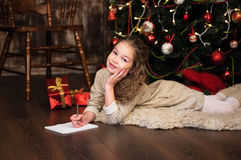 Girl writes letter to santa Stock Images
