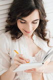 Girl writes in a notebook in bed Royalty Free Stock Photography