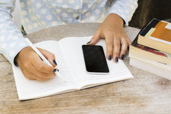 Girl writes in a notebook, with cell phone and books on the tabl Royalty Free Stock Photo