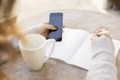 Girl writes in a notebook, with cell phone and cup of coffee Stock Photos