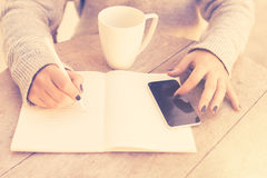 Girl writes in a notebook, with cell phone and cup of coffee Royalty Free Stock Photos