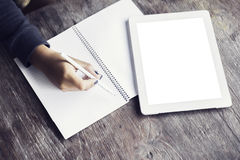 Girl writes in a notebook lying beside a blank digital tablet Stock Images