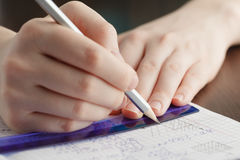 Girl writes in a notebook mathematical formulas Stock Images