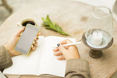 Girl writes in a notebook and uses cell phone Stock Photography