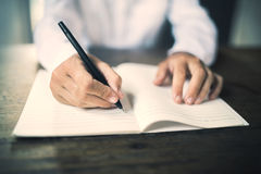 Girl writes in notebook on a wooden table Stock Photo