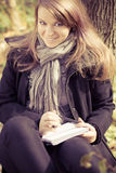 A girl writes on a pad in the park. Outdoors shooting Stock Photos