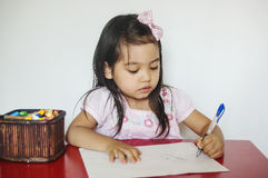 Girl writes on paper. Girl is learning how to use pen and she writes by left hand side Stock Image