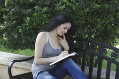Girl writes in park Royalty Free Stock Photography