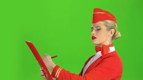 Girl writes a pen in a special folder, she is a flight attendant. Green screen. Side view. Girl writes a pen with a special folder, she is a stewardess smiling stock video