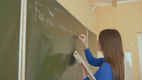 A girl writes on a school board during an English lesson. A girl writes on a school board during an English lesson stock video