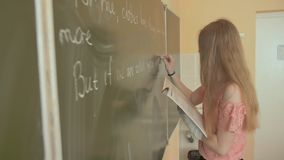 A girl writes on a school board during an English lesson. A girl writes on a school board during an English lesson stock video footage
