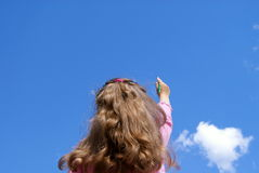 The girl writes in the sky. The girl the-artist draws a pencil in the dark blue sky with clouds in the summer Royalty Free Stock Images