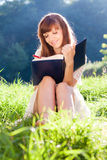 Girl writes something in a book sitting at grass. Person stock images