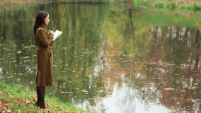 Girl Writes Standing By The Lake stock footage