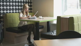 Girl writes text in daily log during coffee break. Smiling model girl aged 20s sitting at the cafe writes text in a daily log during coffee break stock video footage