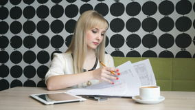 Girl writes text on paper sheets. Smiling model girl aged 20s sitting at the cafe writes text on paper sheets during coffee break stock video