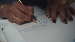 The girl writes the text of the wishes at the event. Close-up. Of a hand with a ballpoint pen in it stock footage