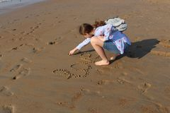 The girl writes the word `Love` and a symbol of heart on the sand at sunset. Footprints on the sea sand. stock photos