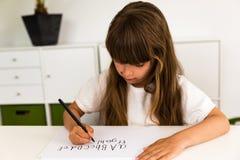 Girl writing the ABC alphabet Stock Photos