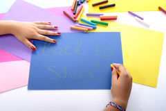 A girl writing back to school on blue paper Royalty Free Stock Photos