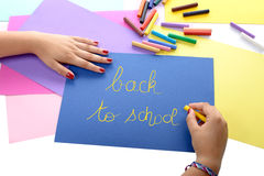 A girl writing back to school on blue paper Stock Images