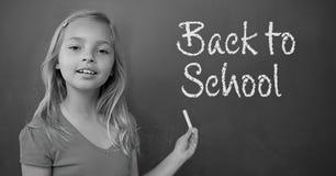 Girl writing Back to school text on blackboard Stock Photography