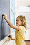 Girl Writing on Blackboard Royalty Free Stock Photography