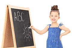 Girl writing on a blackboard with chalk Royalty Free Stock Photography