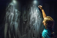 Girl Writing on the Blackboard. Girl child writing on the blackboard wall Stock Image