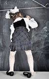 Girl writing on blackboard. Girl in school uniform writing on the blackboard Stock Photo