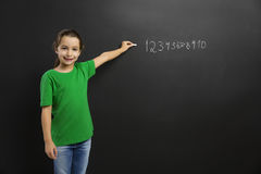 Girl writing in a blackboard Royalty Free Stock Photos