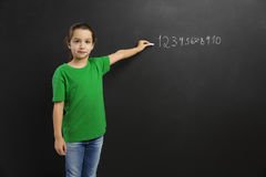 Girl writing in a blackboard. Smart little girl writing in a blackboard, with copy space Royalty Free Stock Photo