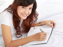 Girl writing on book Royalty Free Stock Photography