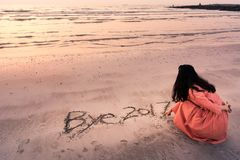 Girl writing Bye 2017 note in the sand Royalty Free Stock Photo