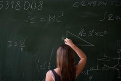 Girl writing on the chalkboard Stock Images