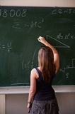 Girl writing on the chalkboard Royalty Free Stock Images