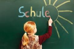 Girl writing on the chalkboard. Little girl writing on the chalkboard royalty free stock images