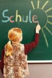 Girl writing on the chalkboard. Young girl writing on the chalkboard royalty free stock photo
