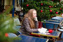 Girl writing Christma postcards in Parisian cafe Royalty Free Stock Photo