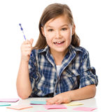 Girl is writing on color stickers using pen Stock Photography