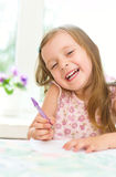 Girl writing. Cute happy little girl writing something in her notebook Royalty Free Stock Photo