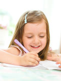 Girl writing. Cute happy little girl writing something in her notebook Stock Images