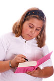 Girl Writing In Diary. A young girl writing in her pink diary, isolated against a white background Stock Photography