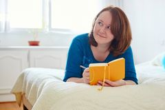 Girl writing into diary or planning her day Royalty Free Stock Image