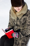 Writing in a diary with smile. A girl is writing in a diary with smile sitting on a behch in winter Royalty Free Stock Photo