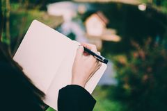 Girl writing down her thoughts in a notebook against tiny blurred swan house in a middle of a pond in a park. Pale hand and colorful background royalty free stock image