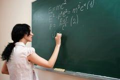 Girl writing formula Stock Images